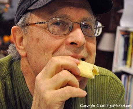 senior man with a baseball cap enjoying a cookie