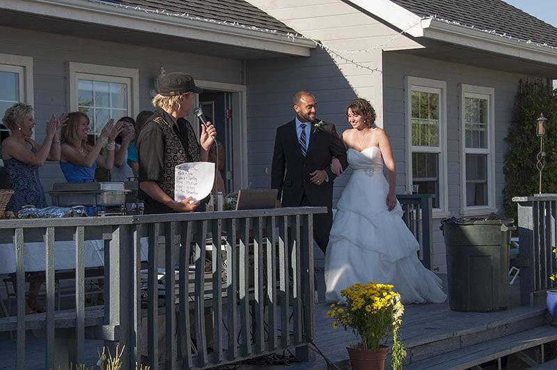 bride on groom's arm walk across deck to happy applause
